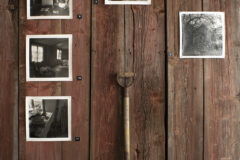 A group of photographs exhibited on reclaimed wall timbers from collapsed house.